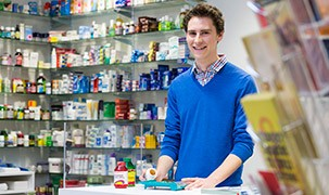 Student standing next to a pharmacy in campus