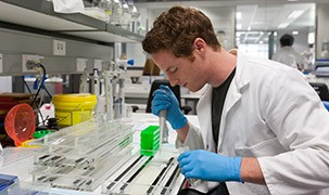 Image of student in a lab coat in a lab