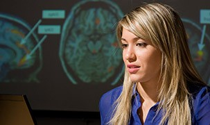 Image of student with schemetics of brains behind her