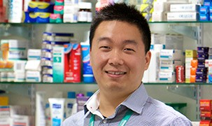 Image of student with pharmacy behind him