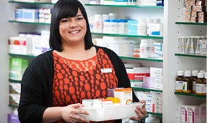 Image of student in front of a campus pharmacy holding medicines